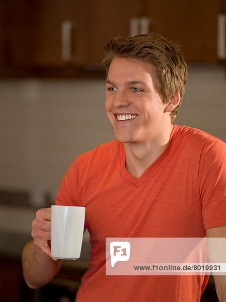 Young man holding cup of coffee in kitchen