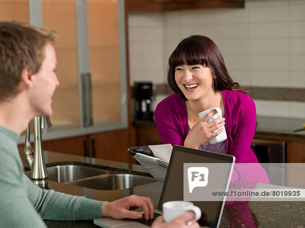 Junges Paar bei Kaffee und Laptop in der Küche  lächelnd