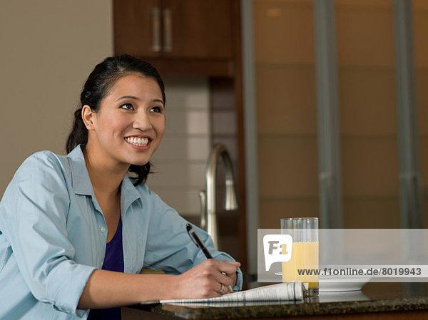 Junge Frau liest Zeitung über Orangensaft  lächelnd