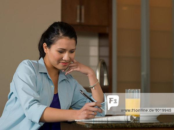 Junge Frau liest Zeitung über Orangensaft