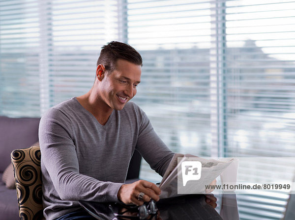 Mid adult man sitting and reading newspaper