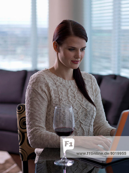 Young woman using laptop with a glass of wine