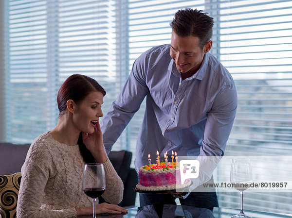 Mid adult man giving young woman birthday cake