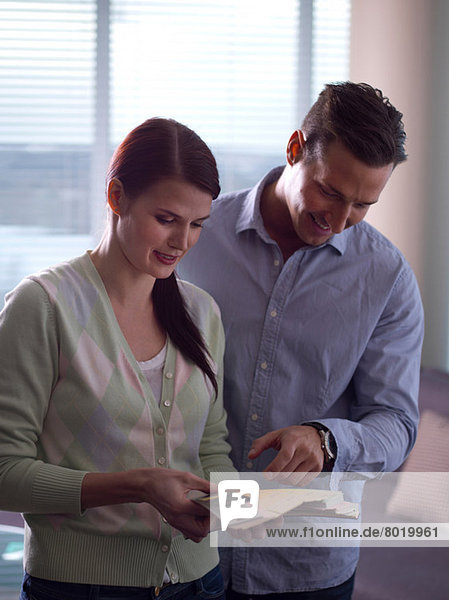 Young woman and mid adult man looking at colour swatches
