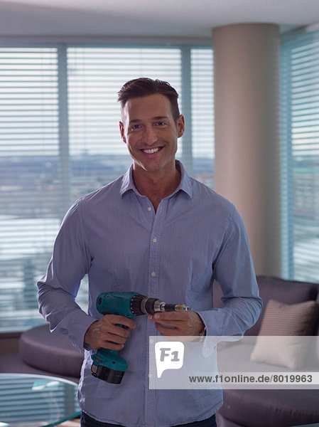 Mid adult man holding hand drill  portrait