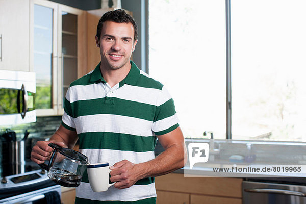 Young man pouring coffee from pot in kitchen  portrait