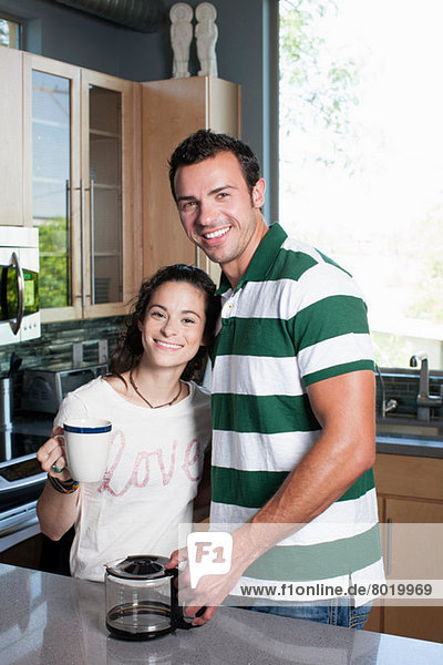 Young couple enjoying coffee in kitchen  portrait