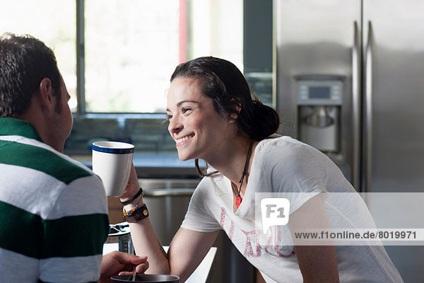 Young couple enjoying coffee in kitchen  smiling