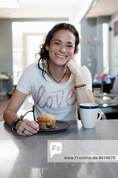 Young woman enjoying coffee and muffin in kitchen  portrait