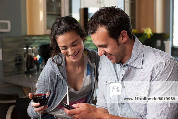 Young couple holding wine glass and looking at mobile phone