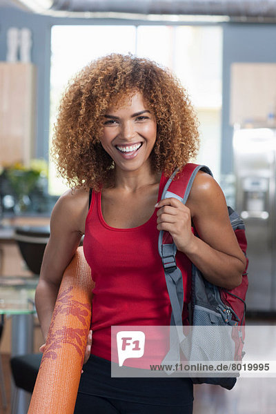 Mittlere erwachsene Frau mit Yogamatte und Wasserflasche  Portrait