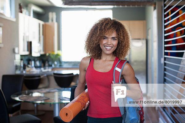 Mittlere erwachsene Frau in roter Weste und Yogamatte  Portrait