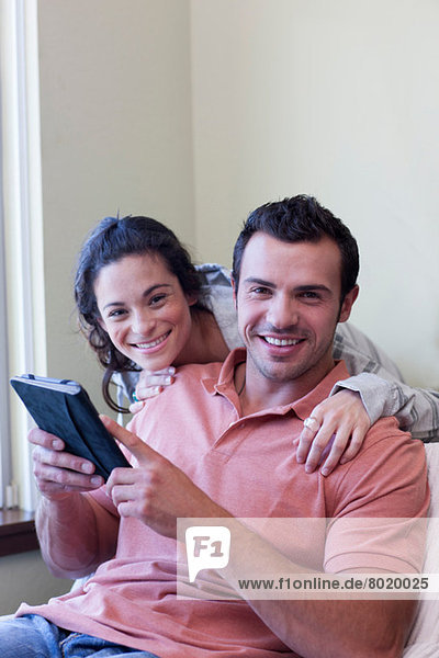 Young couple using electronic book  portrait