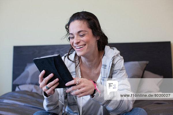 Junge Frau sitzend Bett lesend elektronisches Buch  lächelnd