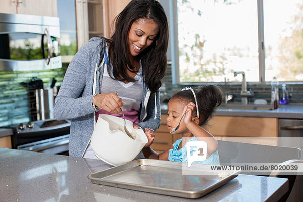 Mittlere erwachsene Frau beim Backen mit Tochter in der Küche