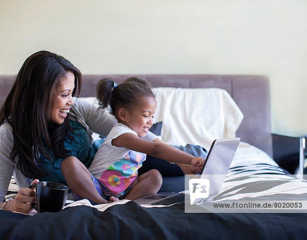 Mutter und Tochter mit Laptop im Bett