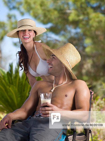 Junges Paar mit Sonnenhut und Entspannung im Urlaub  Portrait