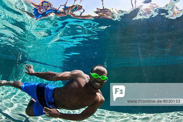 Junger Mann schwimmt unter Wasser im Pool  Portrait