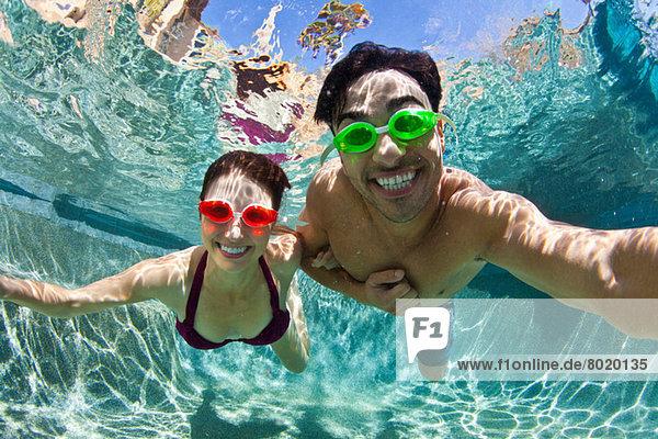 Junges Paar schwimmt unter Wasser im Pool