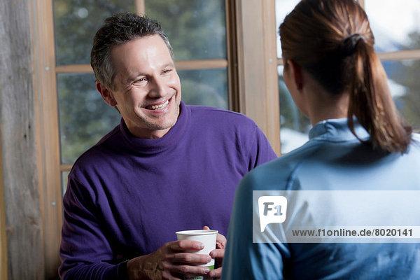 Junge Frau und reifer Mann mit heißem Getränk drinnen  lächelnd