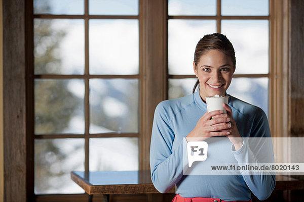 Junge Frau mit heißem Getränk im Haus