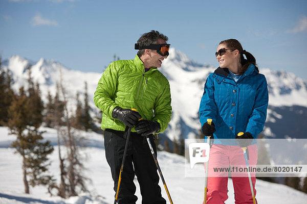 Junge Frau und reifer Mann in Skibekleidung mit Skistöcken