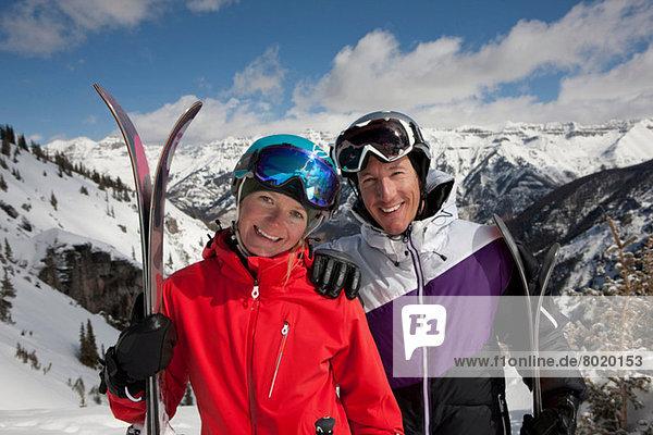 Mittlerer Erwachsener Mann in und junge Frau in Skibekleidung mit Skiern  Portrait