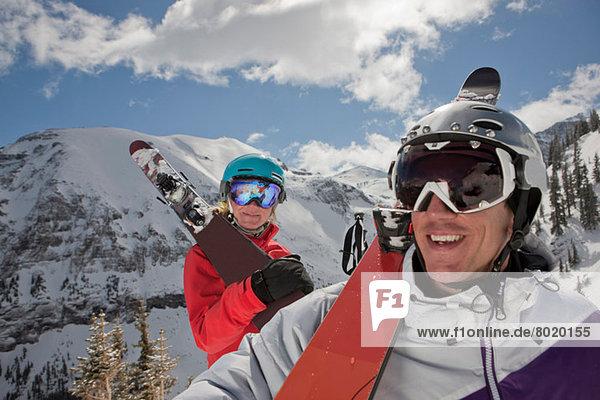 Junge Frau und mittelgroßer Mann in Skibekleidung mit Skiern auf der Schulter  lächelnd