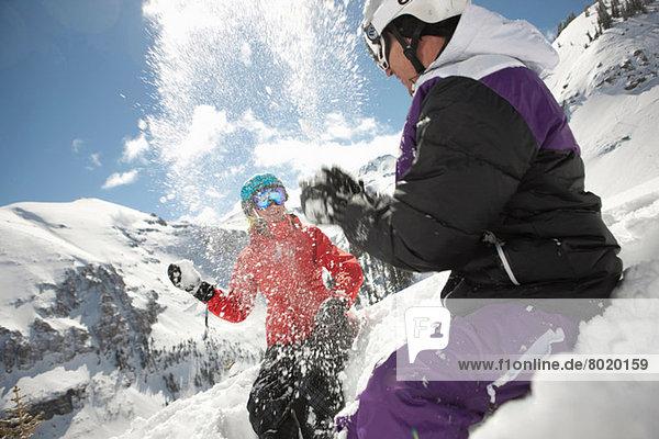 Mittlerer Erwachsener Mann und junge Frau in Skibekleidung mit Schneeballschlacht