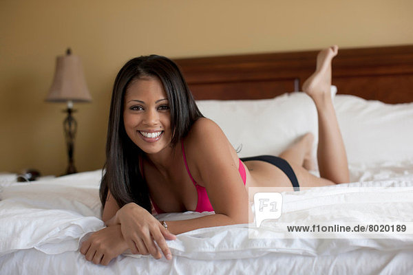 Young woman lying on bed in underwear  portrait
