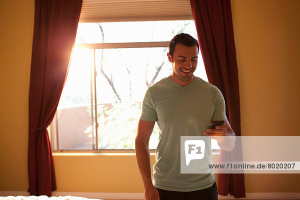 Young man looking at mobile phone in hotel room  smiling