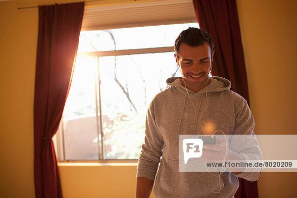 Junger Mann hört mp3-Player im Hotelzimmer  lächelnd