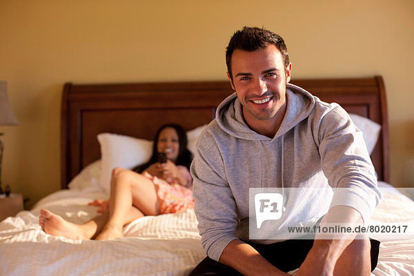 Young man sitting on bed in hotel room  smiling