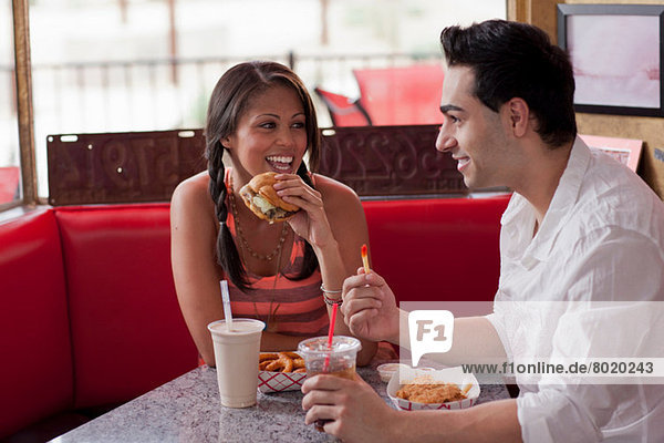 Young couple eating fast food in diner