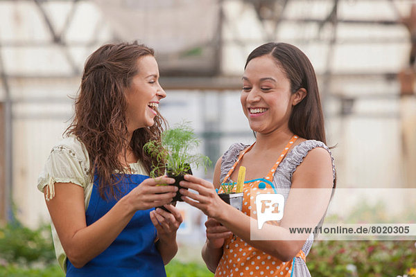 Young women holding plant in garden centre  smiling