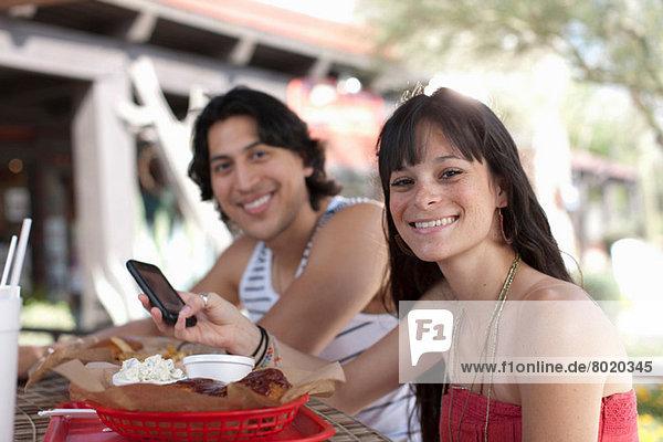 Junge Frau mit Handy im Outdoor-Café  lächelnd