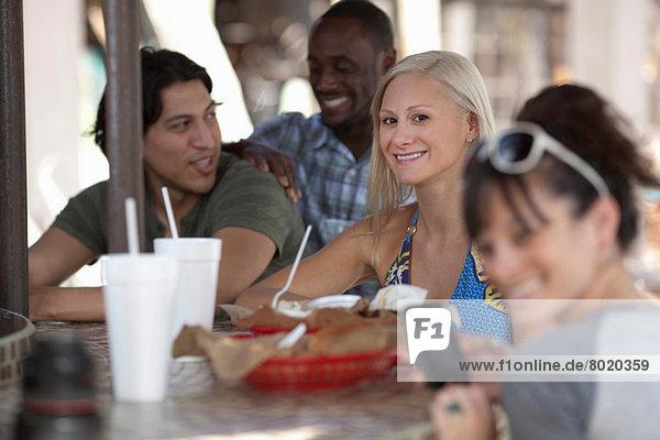 Junge Freunde sitzen zusammen im Café im Freien  Portrait
