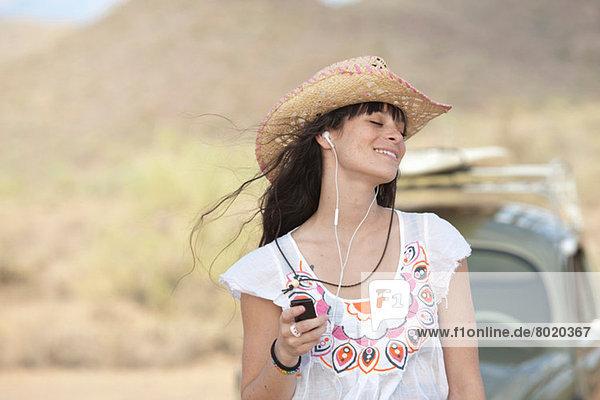 Junge Frau mit Cowboyhut und Kopfhörer  lächelnd