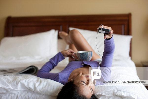 Reife Frau  die auf dem Bett liegt und dem MP3-Player lächelnd zuhört.