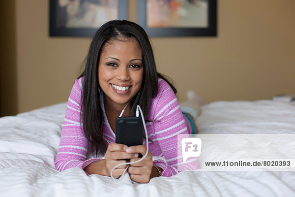 Junge Frau auf dem Bett liegend und mp3-Player hörend  Portrait