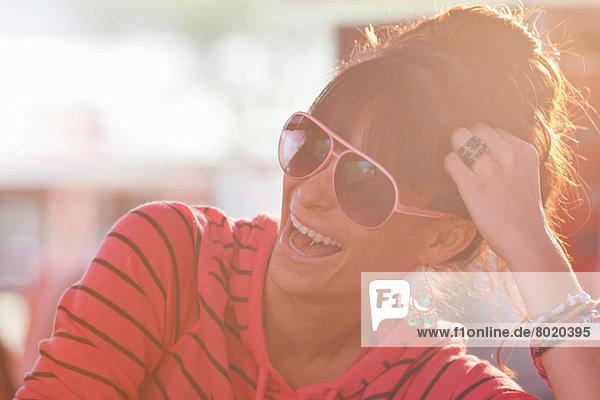 Junge Frau mit Sonnenbrille im sonnendurchfluteten Diner
