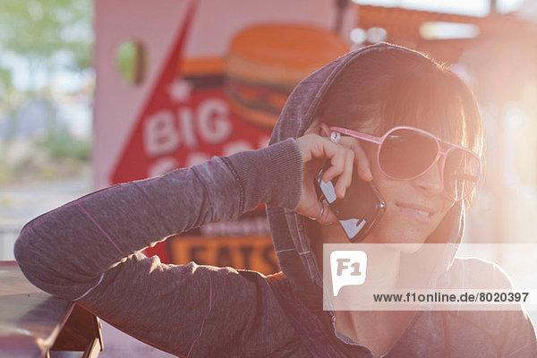 Junge Frau in Sonnenbrille mit Handy im sonnendurchfluteten Restaurant