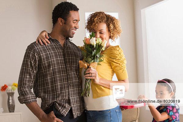 Mann schenkt Frau Blumen  Tochter nimmt Schokolade