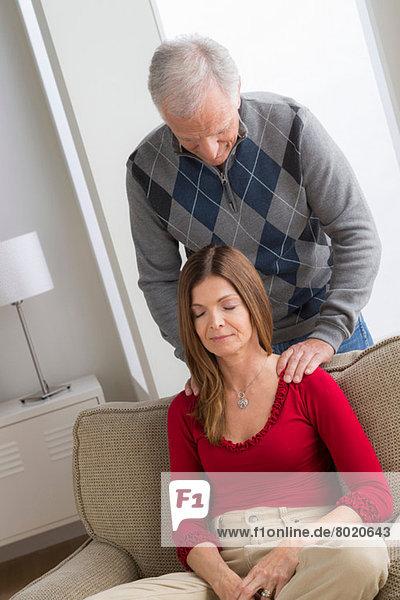 Älterer Mann massiert die Schultern der Frau.