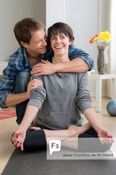 Woman doing yoga at home  man hugging her