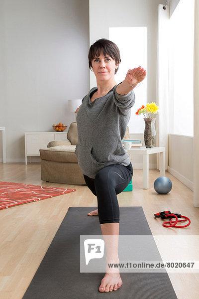 Mittlere erwachsene Frau beim Yoga zu Hause