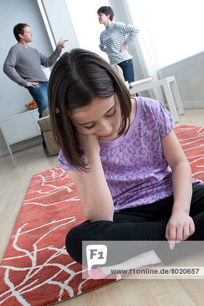 Girl sitting on floor with parents arguing in background