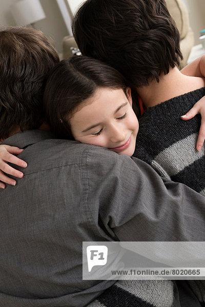 Eltern umarmen Tochter