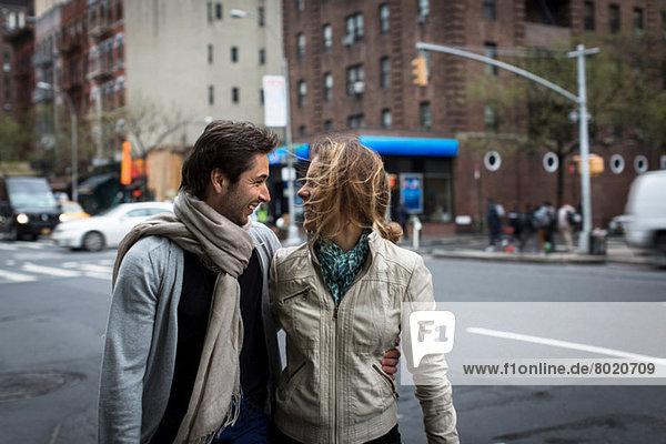 Lächelndes Paar  das zusammen die Straße entlang geht.