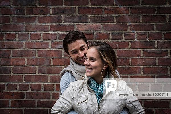 Porträt des lächelnden Paares vor der Ziegelwand